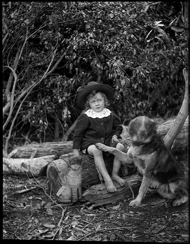 Bare foot boy wearing a hat, seated on a log_3169118372_m