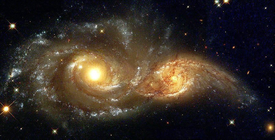 The larger and more massive galaxy is cataloged as NGC 2207 (on the left in the Hubble Heritage image), and the smaller one on the right is IC 2163. Strong tidal forces from NGC 2207 have distorted the shape of IC 2163, flinging out stars and gas into long streamers stretching out a hundred thousand light-years toward the right-hand edge of the image. Computer simulations, carried out by a team led by Bruce and Debra Elmegreen, demonstrate the leisurely timescale over which galactic collisions occur. In addition to the Hubble images, measurements made with the National Science Foundation's Very Large Array Radio Telescope in New Mexico reveal the motions of the galaxies and aid the reconstruction of the collision. The calculations indicate that IC 2163 is swinging past NGC 2207 in a counterclockwise direction, having made its closest approach 40 million years ago. However, IC 2163 does not have sufficient energy to escape from the gravitational pull of NGC 2207, and is destined to be pulled back and swing past the larger galaxy again in the future. The high resolution of the Hubble telescope image reveals dust lanes in the spiral arms of NGC 2207, clearly silhouetted against IC 2163, which is in the background. Hubble also reveals a series of parallel dust filaments extending like fine brush strokes along the tidally stretched material on the right-hand side. The large concentrations of gas and dust in both galaxies may well erupt into regions of active star formation in the near future. Trapped in their mutual orbit around each other, these two galaxies will continue to distort and disrupt each other. Eventually, billions of years from now, they will merge into a single, more massive galaxy. It is believed that many present-day galaxies, including the Milky Way, were assembled from a similar process of coalescence of smaller galaxies occurring over billions of years. This image was created from 3 separate pointings of Hubble. The Wide Field Planetary Camera 2 data